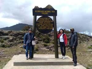 Family outside Shira Base Camp sign hiking one day to Shira Plateau on Mount Kilimanjaro